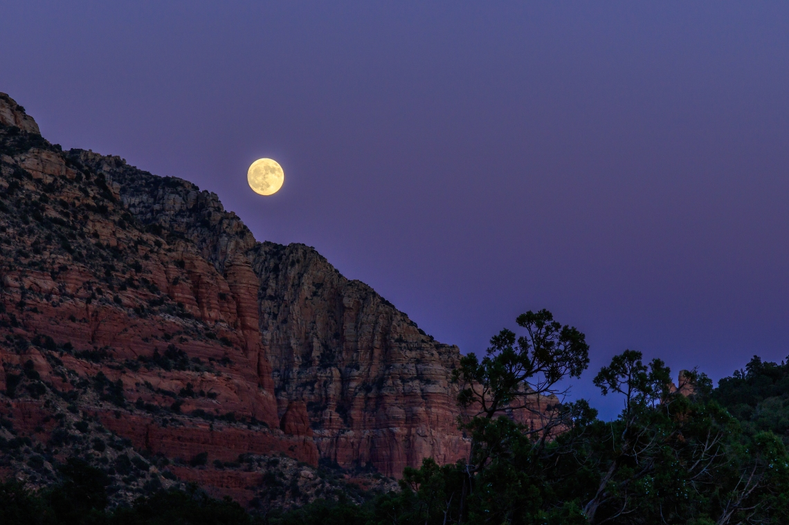 Moonrise at sunset over the red rock of