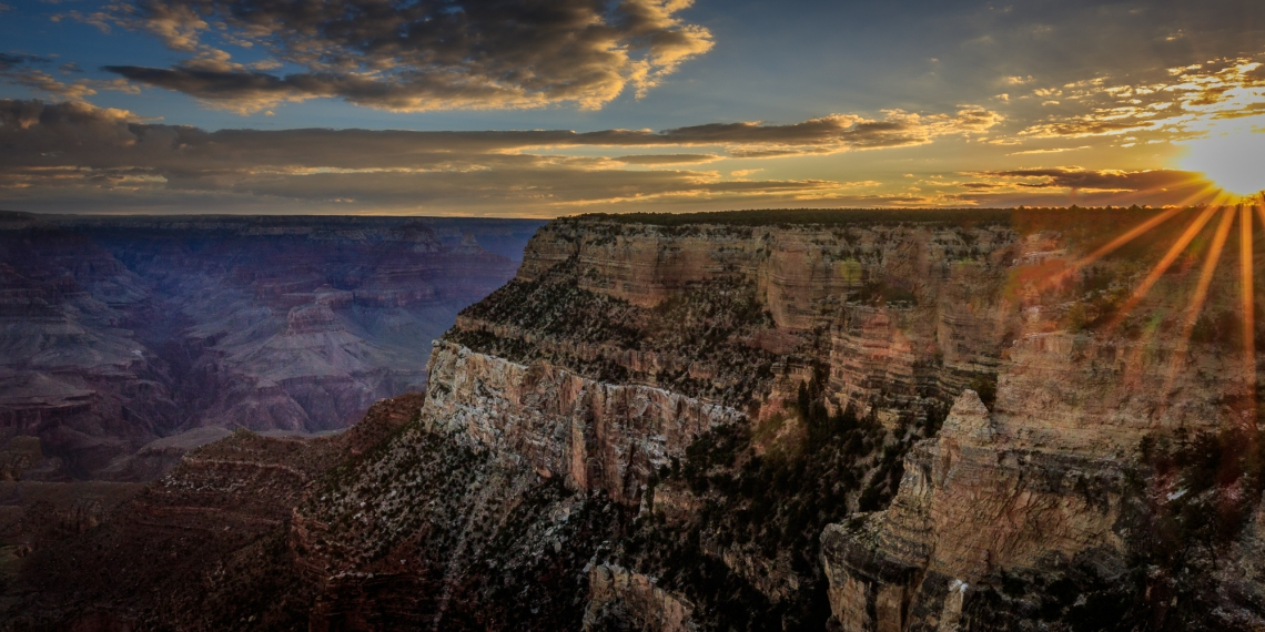 Sunrise suddenly blasts through above the clouds at Grand Canyon National Park